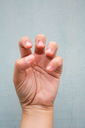 Trigger Finger lock on fingers of woman's front left hand, Suffering from pain, On Blue-grey colour background,  Close up & Macro shot, Office syndrome, Health care concept Stok Fotoğraf