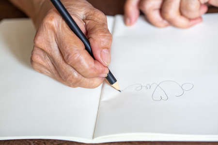 """Senior woman's right Hand writing letter """"LOVE"""""""