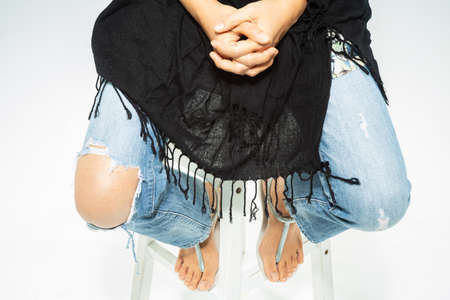 Womans hands praying on Black scarf background, Torn denim blue jeans at the knee with lady leg on white background, Close up & Macro shot, Selective focus, Symbol, Gesturing, Body Language concept