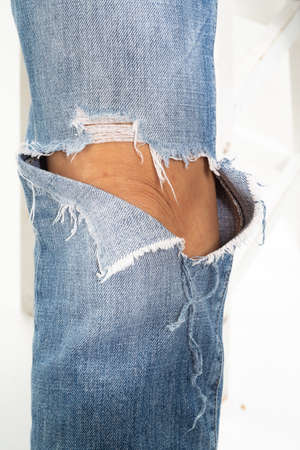 Jean bleu denim déchiré au genou avec jambe de dame sur fond blanc, gros plan et photo macro, mise au point sélective, partie de la peau du corps