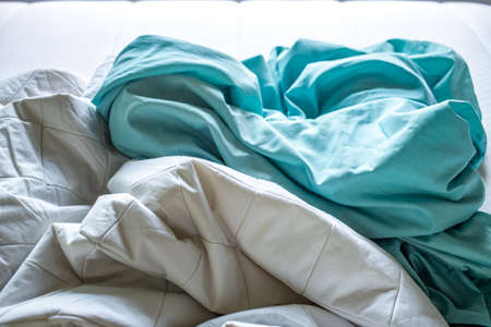 Turquoise and White crumpled bed sheet on white bed, Close up shot, Selective focus, Bedroom cleaning concept Stock Photo
