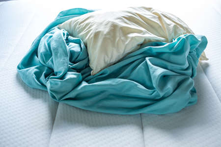 Turquoise crumpled bed sheet with ivory pillow on white bed, Close up shot, Selective focus, Bedroom cleaning concept