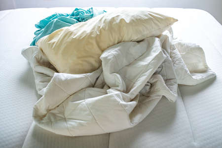Turquoise and White crumpled bed sheet, Ivory pillow on white bed, Close up shot, Selective focus, Bedroom cleaning concept