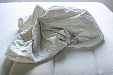 White crumpled bed sheet on white bed, Close up shot, Selective focus, Bedroom cleaning concept 免版税图像