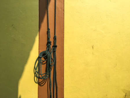 Green ropes is hanging on yellow with brown cement wall background, Light & Shadow concept