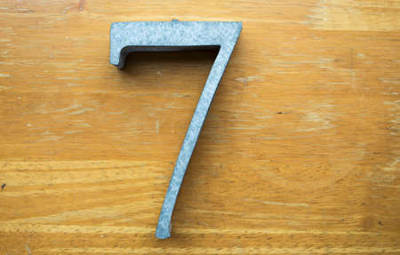Number 7 (seven) made  from galvanized iron on wood texture background 写真素材