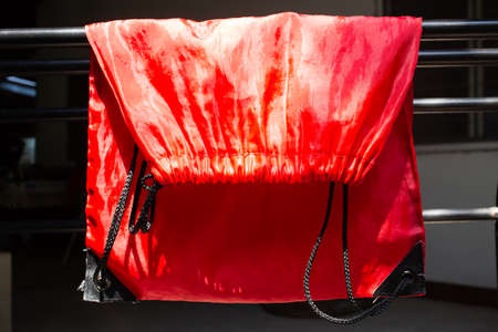Dry Polyester Tote Bag in the sun, Red glossy texture backgroud, Close up & macro shot, Sport  bag concept