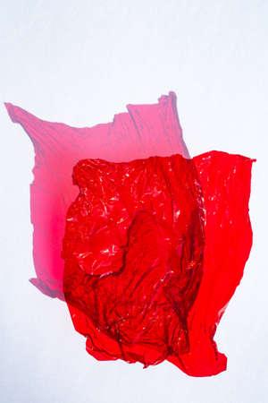 Hoja delgada de celofán de color rojo con textura de superficie arrugada brillante sobre fondo blanco, concepto abstracto, luz y sombra