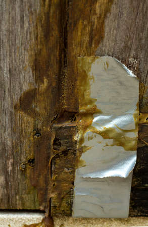 Damaged wooden door, Wooden door repaired by glue and gray adhesive tape, Close up & Macro shot, Selective focus
