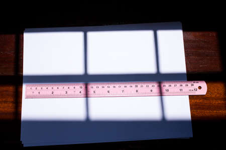 White paper with pink ruler on wood texture background, Light and shadow Фото со стока