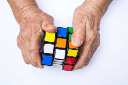 Bangkok, Thailand, 06 May 2018, Rubiks cube in old womans hand isolated on white background, Old woman holding Rubiks cube and playing with it, Rubiks cube invented by a Hungarian architect Erno Rubik in 1974 Publikacyjne