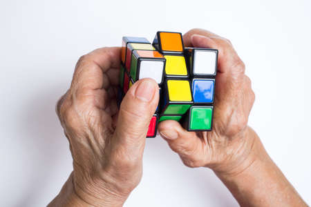 Bangkok, Thailand, 06 May 2018, Old woman holding Rubiks cube and playing with it, isolated on white background, Rubiks cube invented by a Hungarian architect Erno Rubik in 1974 Publikacyjne