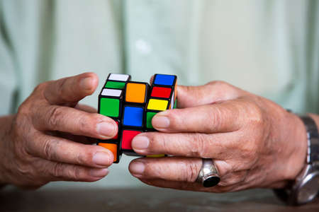 Bangkok, Thailand, 23 March 2019, Old man holding Rubiks cube and playing with it, on wooden texture background, Rubiks cube invented by a Hungarian architect Erno Rubik in 1974, Close up & Macro shot, Selective focus