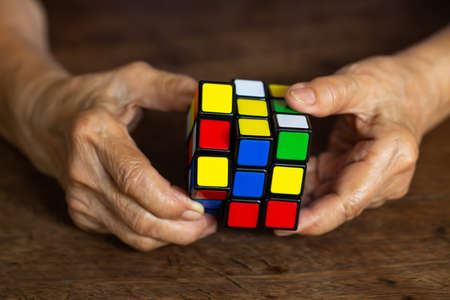 Bangkok, Thailand, 23 March 2019, Old woman holding Rubiks cube and playing with it, on wooden texture background, Rubiks cube invented by a Hungarian architect Erno Rubik in 1974, Close up & Macro shot, Selective focus