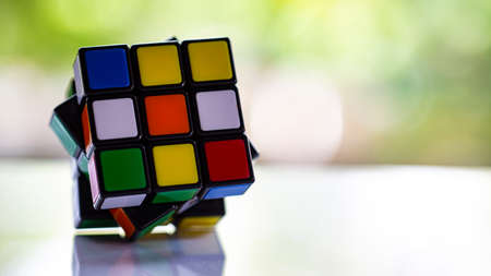 Bangkok, Thailand, 08 June  2019, Rubiks cube on white acrylic texture, Bokeh green garden background, Rubiks cube invented by a Hungarian architect Erno Rubik in 1974, Close up & Macro shot, Selective focus Publikacyjne