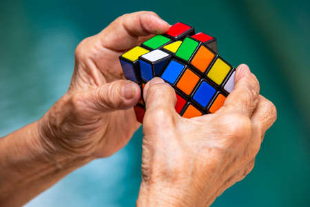 Bangkok, Thailand, 27 July 2019, Old woman holding Rubiks cube and playing with it, in bokeh blue texture background, Rubiks cube invented by a Hungarian architect Erno Rubik in 1974, Close up shot Publikacyjne