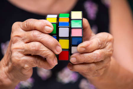Bangkok, Thailand, 27 July 2019, Old woman holding Rubik's cube and playing with it, in bokeh  texture background, Rubik's cube invented by a Hungarian architect Erno Rubik in 1974, Close up shot Zdjęcie Seryjne - 136922137