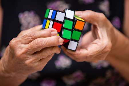Bangkok, Thailand, 27 July 2019, Old woman holding Rubiks cube and playing with it, in bokeh  texture background, Rubiks cube invented by a Hungarian architect Erno Rubik in 1974, Close up shot