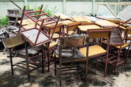 Abandoned broken vintage wooden lecture chairs in old school Stock fotó