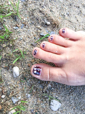 Woman's carmine Nail with white polka dot on sandy Background 写真素材