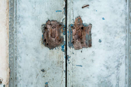 Old rusty lock is damaged with old wooden door, closeup