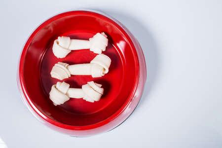 Three dog bones in feeding bowl isolated on white background