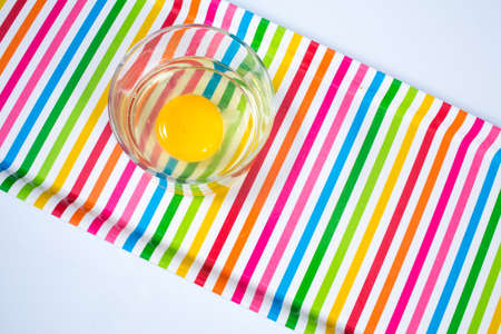 Raw chicken egg in glass bowl on multicolor tray isolated on white background Stok Fotoğraf