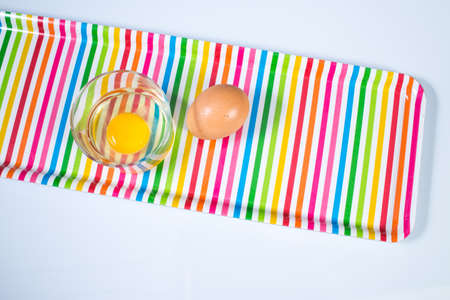 Raw chicken egg in glass bowl with egg on multicolor tray isolated on white background Zdjęcie Seryjne