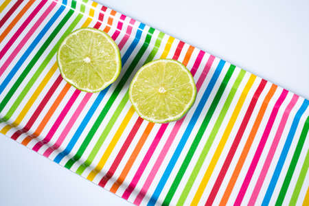 A lime sliced in half  on multicolored tray