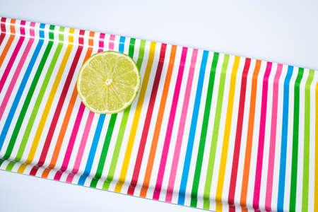 A lime sliced in half  on multicolored tray Zdjęcie Seryjne - 129765900