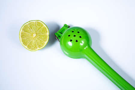 Lemon squeezer and a lime sliced in half isolated on white background Stockfoto