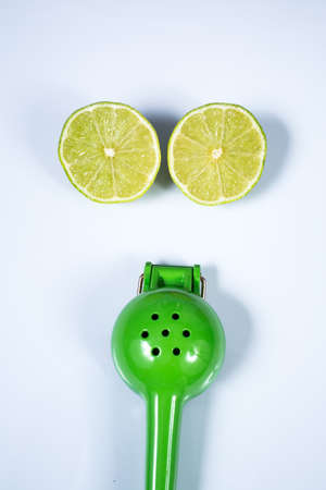 Lemon squeezer and a lime sliced in half isolated on white background Zdjęcie Seryjne - 129765914