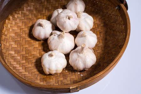Garlic on rattan basket isolated on white background, Garlic on wicker basket isolated on white background, Top view Zdjęcie Seryjne