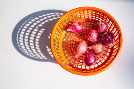 Red onions in orange plastic basket isolated on white background, Top view