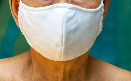 Senior woman wearing DIY handmade cotton cloth mask, Medical mask, Surgical mask in blue background, Front view, Close up shot, Select focus, Prevention from covid19, Coronavirus, Bacteria, Healthcare