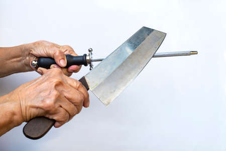 Senior woman's hand holding knife grinder  with knife sharpening on white background, Close up shot, Selective focus, Kitchen utensils concept