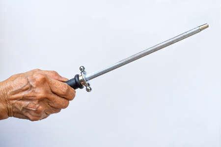 Senior woman's hand using a knife grinder on white background, Close up shot, Kitchen utensils concept