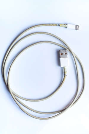 Damaged white usb cable plug and micro usb plug or Old Smart Phone Charger Cable broken on white acrylic background, Close up & Macro shot, Select focus, Technology, Business concept