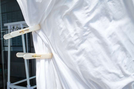 White bedsheet drying in the sun, White clothespins, White coat hanger in house, Wrinkled texture, Abstract background, Close up shot, Selective focus, Housework, Laundry concept