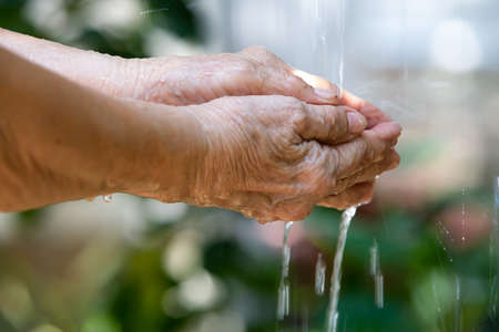 Senior woman washing her hands in bokeh green garden background, Close up & Macro shot, Selective focus, Prevention from covid19, Bacteria, Healthcare concept