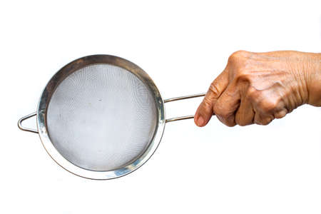 Senior woman's left hand holding Colander, Stainless sieve for cooking on white background, Close up shot, Selective focus, Kitchen utensils concept Stock Photo