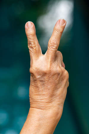 Senior woman's right hand raise two fingers up in bokeh blue swimming pool background, Close up & Macro shot, Selective focus, Asian body skin part, Symbol, Gesturing, Body Language concept