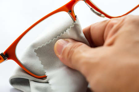Woman's right hand cleaning orange shortsighted or nearsighted eyeglasses by grey microfibre cleaning cloths, On white background, Close up & Macro shot, Selective focus, Optical concept