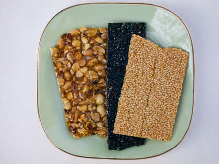Nut Bars, Peanut Bars, Black and White sesame seeds bars on green plate, Close up and macro shot, Snack food Zdjęcie Seryjne