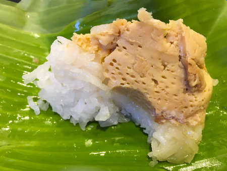 Sticky rice with steamed egg custard eaten, wrapped in banana leaf package, Thai dessert