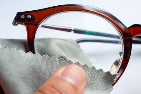 Woman's left hand cleaning shortsighted or nearsighted eyeglasses by microfibre cleaning cloths, On white background, Close up & Macro shot, Selective focus, Optical concept