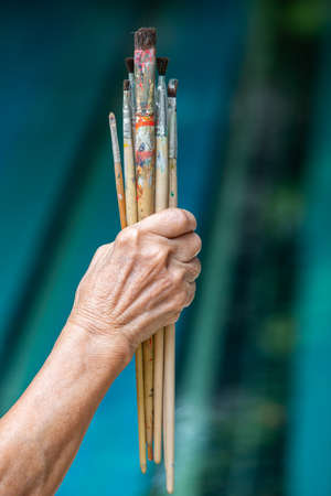 Senior woman's hand holding old paintbrushes in bokeh blue swimming pool background, Selective focus, Hobby paint art concept Zdjęcie Seryjne