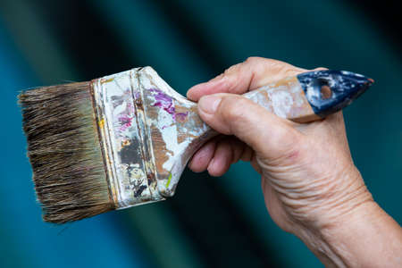 Senior woman's hand holding old paintbrush in bokeh blue swimming pool background, Selective focus, Hobby paint art concept Zdjęcie Seryjne