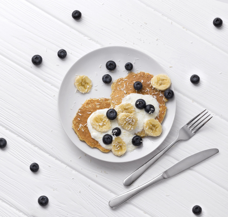 Sweet oatmeal pancakes with cream, blueberry and banana. Healthy Breakfast concept. Organic food on rustic wooden table