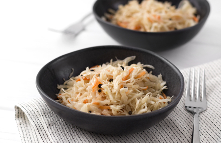 Fermented cabbage. Two plates of traditional russian appetizer sauerkraut with carrot  on white wooden table.